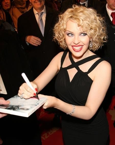 Kylie autographs items for her fans outside the awards