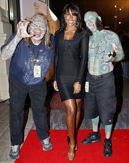 Cat man and Lizardman escort Kelly Rowland down the red carpet