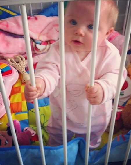 Baby Faith clutched onto the bars of her cot as her proud mummy took a picture