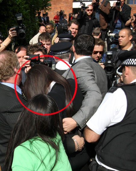 Naomi is pushed through a crowd of photographers