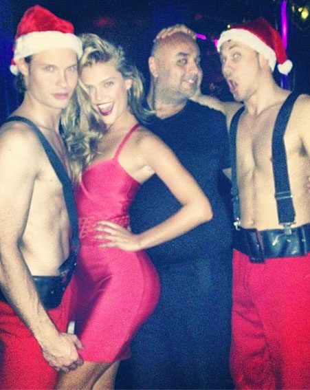 The Victoria's Secret model got into the festive spirt with two half-naked santas
