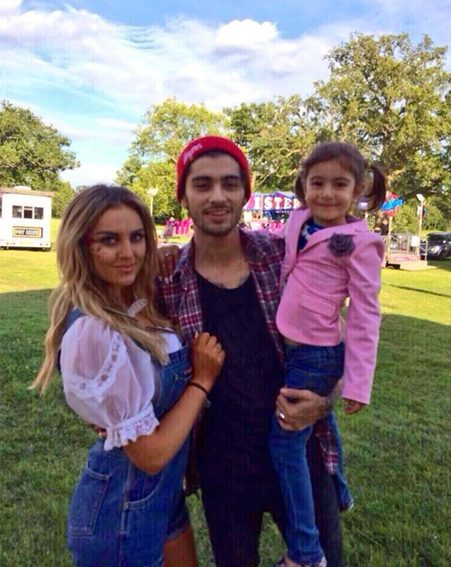 Perrie beams as she cuddles up to her fiancé Zayn Malik in front of the funfair he arranged for her 21st birthday