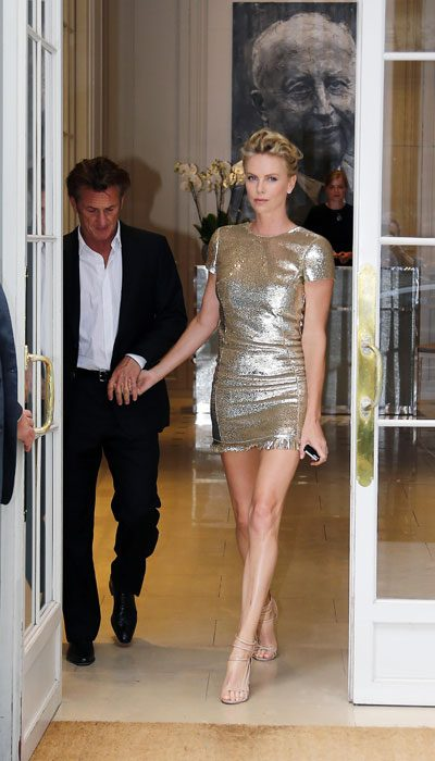 Charlize Theron was with Sean Penn and she wore gold to the Dior Couture show in Paris