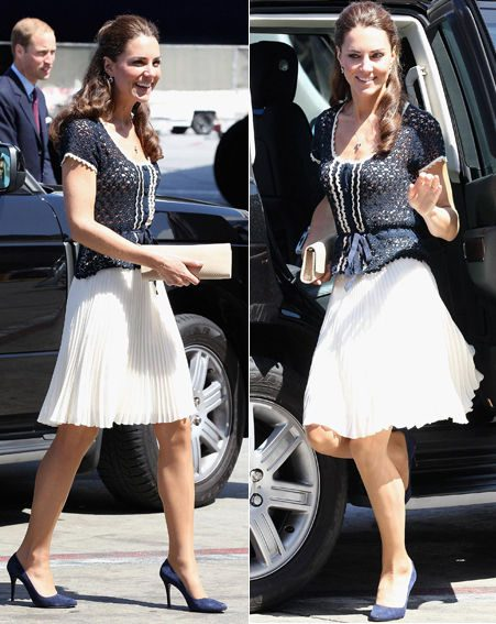 Kate Middleton wearing a blue blouse and pleated white skirt with matching heels