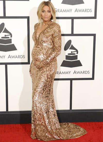 The mum-to-be proudly paraded her pregnancy curves at the GRAMMYs 2014 in a stunning gold frock