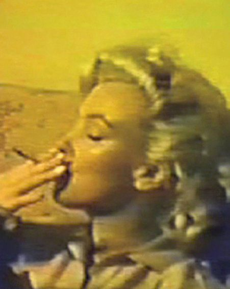 The blonde star puffs on the marijuana joint in this still from the video