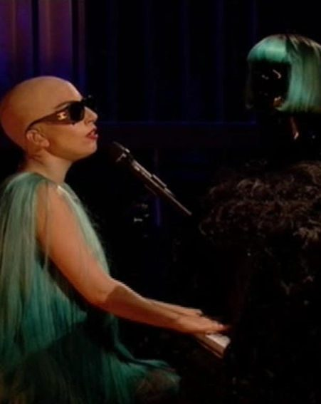 Lady Gaga takes her wig off and places it on her piano