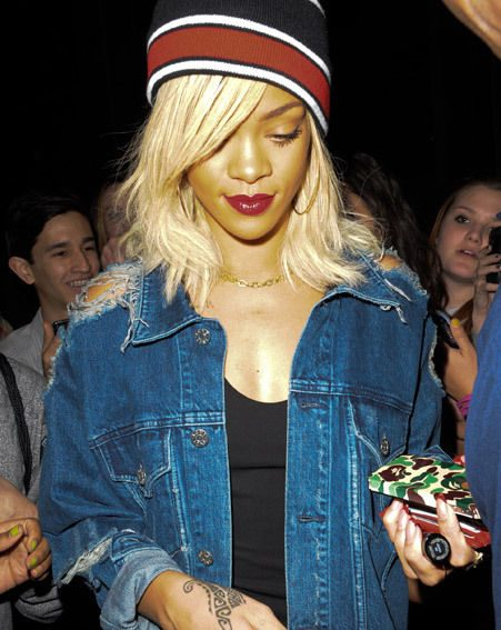 Rihanna appeared with red lipstick and a hat with a ripped denim jacket