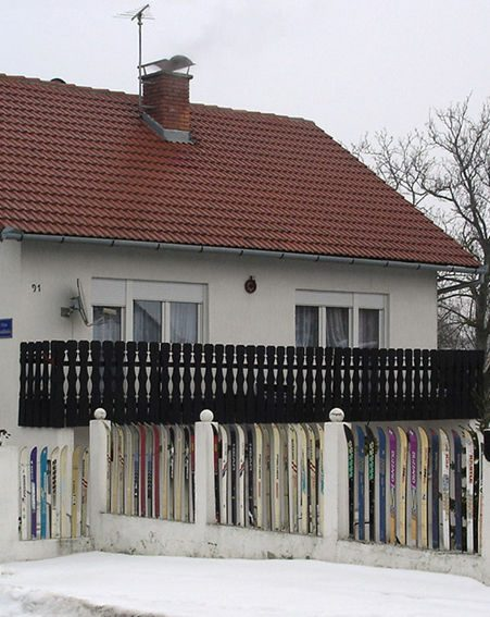 The fence, which snakes round Svalina's home, is made of more than 400 skis
